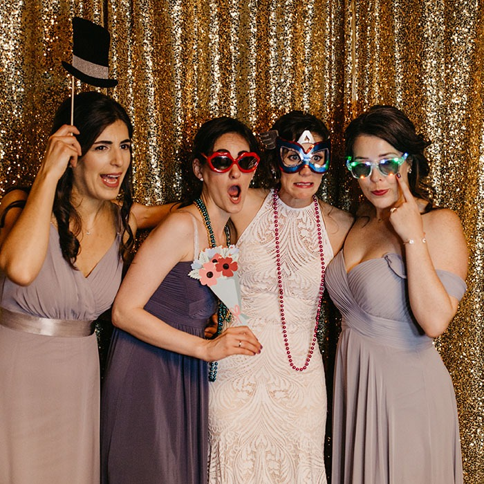 four ladies taking pictures with silly glasses